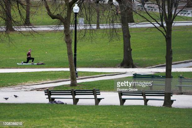 Woman works out in a very quiet Boston Common on March 25, 2020. Massachusetts Gov. Charlie Baker this week issued a stay-at-home advisory for...