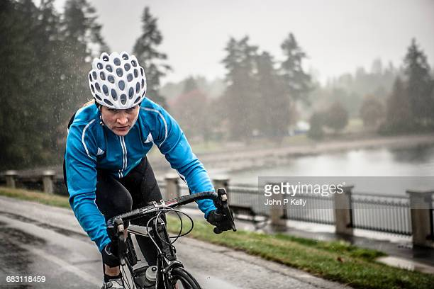 woman works out on her bicycle in the rain - solo adulti foto e immagini stock
