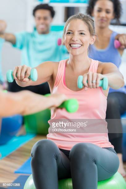 woman works shoulders with hand weights at gym - hand weight stock pictures, royalty-free photos & images