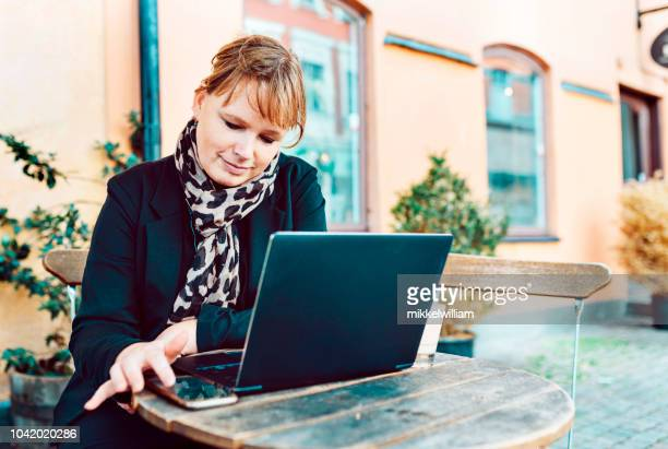 Woman works with her laptop computer and smart phone at outdoor cafe