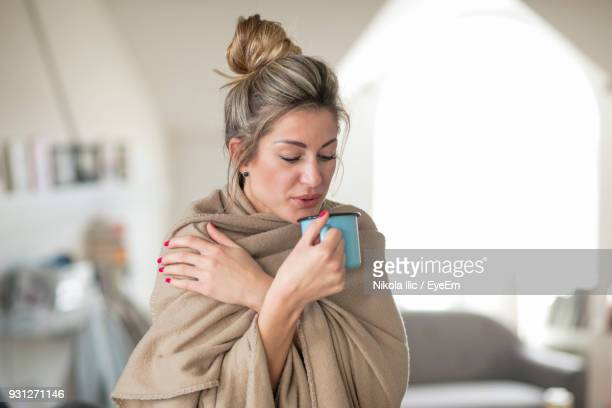 woman wrapped having drink while standing at home - frio fotografías e imágenes de stock