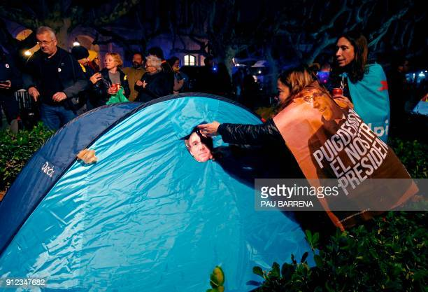 A woman wrapped in a banner reading 'Puigdemont our president' puts a mask depicting the ousted separatist leader on a tent set up outside the...