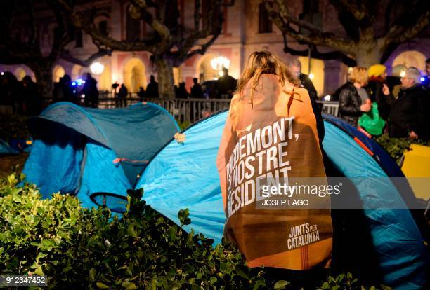 A woman wrapped in a banner reading 'Puigdemont our president' sets up a tent to spend the night outside the Catalan parliament at the Ciutadella...