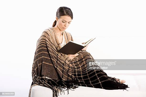 A woman wrapped in a blanket and reading a book