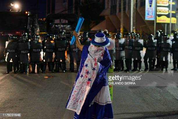 A woman wrapped in a fake bloodstained flag shouts slogans at riot police demanding the resignation of President Juan Orlando Hernandez due to his...