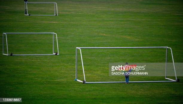 Woman wrapped in a Rainbow flag walks through a football goal on a field in Cologne, western Germany, on June 23, 2021. - With Germany due to play...