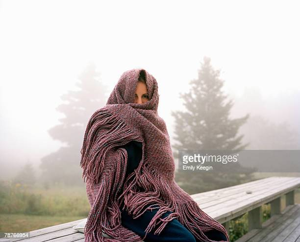 A woman wrapped in a shawl on a misty morning