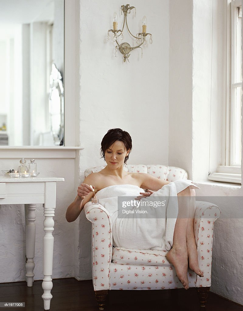 Woman Wrapped in a Towel and Applying Nail Varnish : Stock Photo
