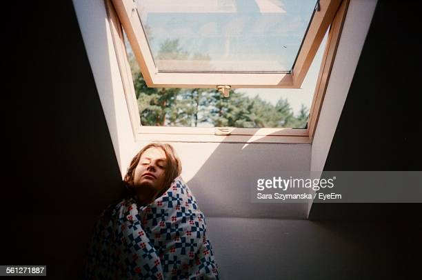 Woman Wrapped In Blanket Against Window