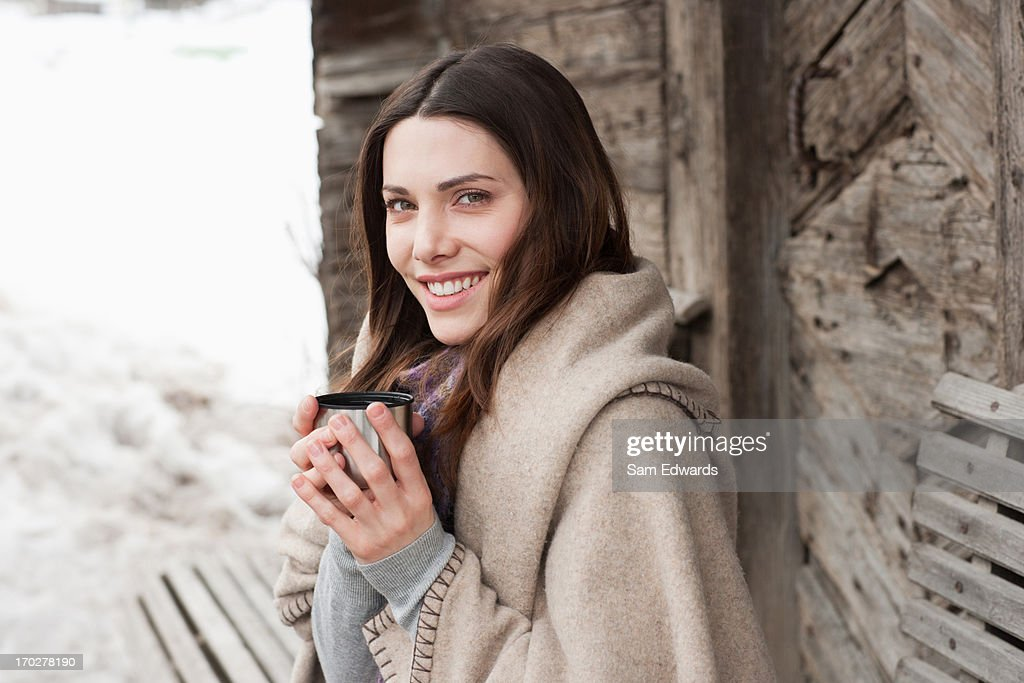 Woman wrapped in blanket drinking coffee : Stock Photo