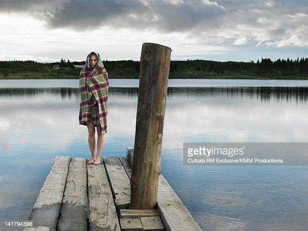 Woman wrapped in blanket on dock