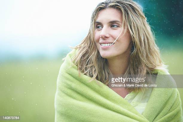 Woman wrapped in blanket outdoors