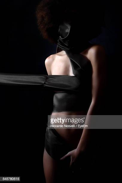 Woman Wrapped In Fabric Against Black Background