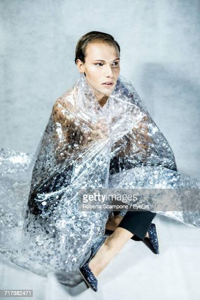 woman wrapped in shiny plastic against gray background - man wrapped in plastic stock pictures, royalty-free photos & images