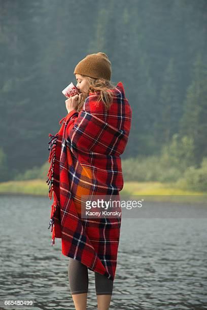 woman wrapped in tartan blanket drinking coffee by lake, mount hood national forest, oregon, usa - schottenkaro stock-fotos und bilder
