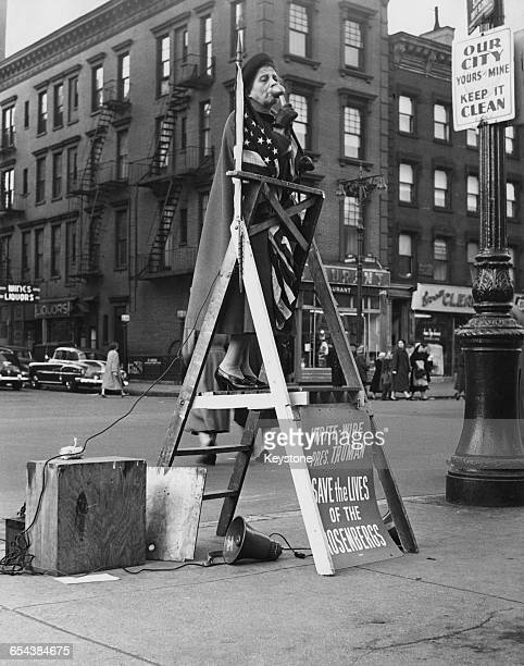 A woman wrapped in the stars and stripes standing on a ladder and using amplification equipment to campaign for clemency for the American couple...