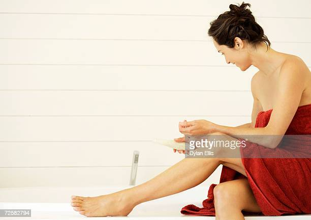 Woman wrapped in towel, holding bottle of bath salts