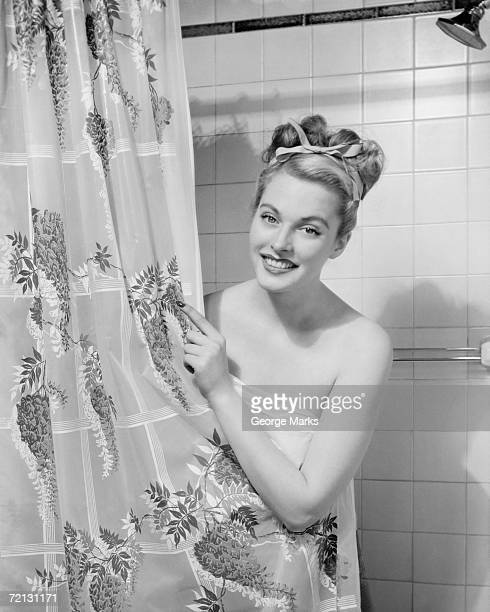 Woman wrapped in towel peeping through shower curtain (B&W), portrait