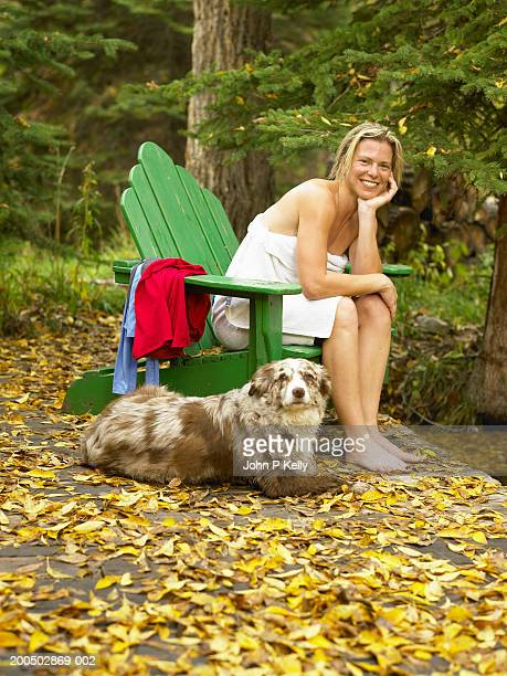 woman wrapped in towel sitting in green chair beside dog, smiling - コロラド州 ニューキャッスル ストックフォトと画像
