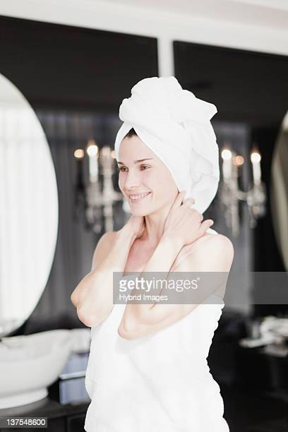 Woman wrapped in towels in bedroom