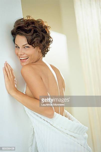 Woman wrapped in white towel in luminous interior