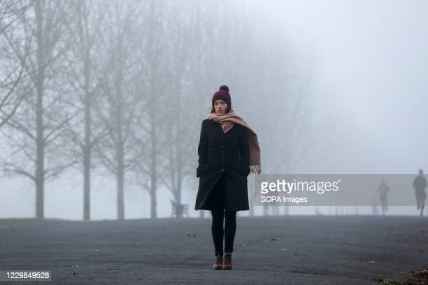 Woman wrapped up warm walk on the street on a foggy and cold morning in London. Freezing cold and foggy weather is forecast across many parts of the...