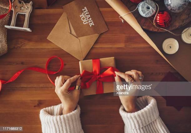 mulher que envolve um presente de natal - cartão de presente - fotografias e filmes do acervo
