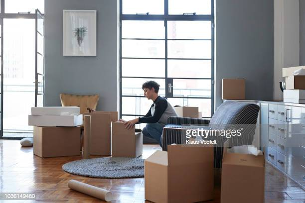 woman wrapping boxes in stylish apartment - physical activity stock pictures, royalty-free photos & images