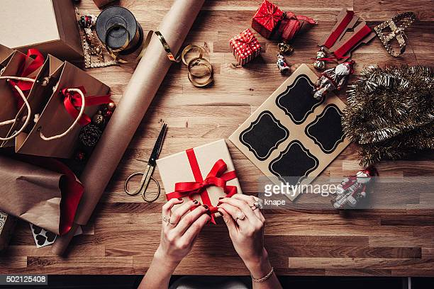 Woman wrapping christmas gifts overhead