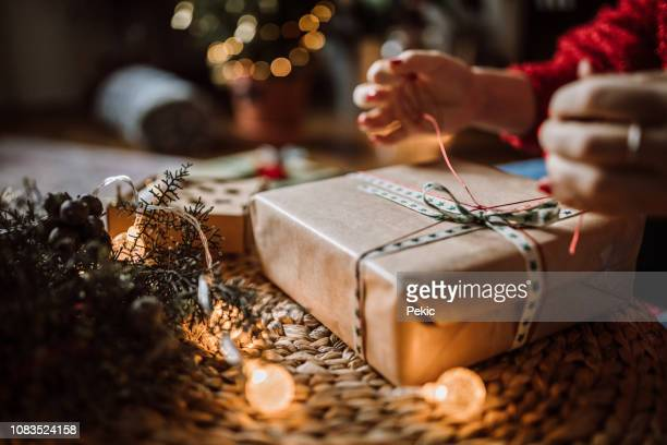 woman wrapping christmas gifts - avvolto foto e immagini stock