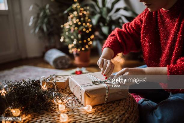 woman wrapping christmas gifts - donna bendata foto e immagini stock