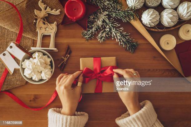 woman wrapping christmas gifts - candela foto e immagini stock