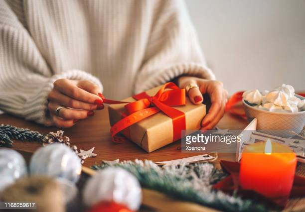 woman wrapping christmas presents at home - donna bendata foto e immagini stock