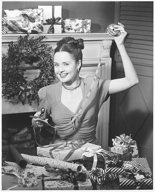 Woman Wrapping Christmas Presents In Living Room, (B&W), Portrait Wall Art