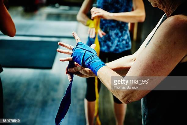 woman wrapping hands before boxing workout - preparation fotografías e imágenes de stock
