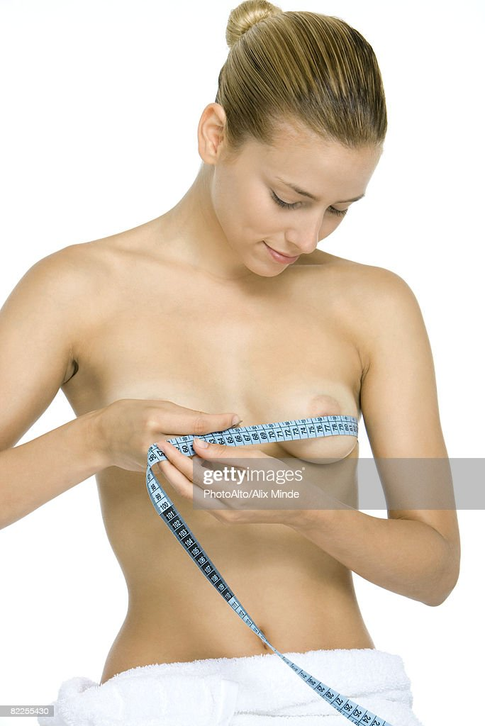 Woman wrapping measuring tape around chest, looking down at breasts, smiling : Stock Photo