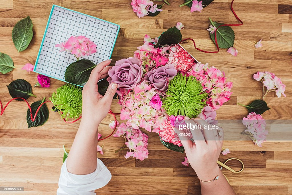 Woman wrapping valentines flowers gifts overhead : Stock Photo