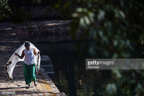 A woman wraps her traditional Ethiopian shawl around herself as she walks alongside the pool at Fasilides Bath ahead of the annual Timkat celebration...