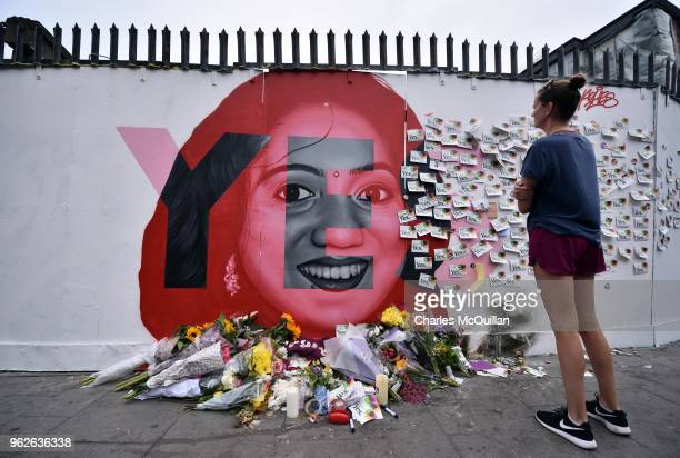 A woman wreads notes left on the Savita Halappanavar mural as the results in the Irish referendum on the 8th amendment concerning the country's...
