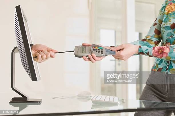 woman wrestling her credit card from card reader - scammer stock pictures, royalty-free photos & images