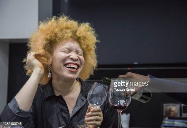 A woman laughing with a wine glass