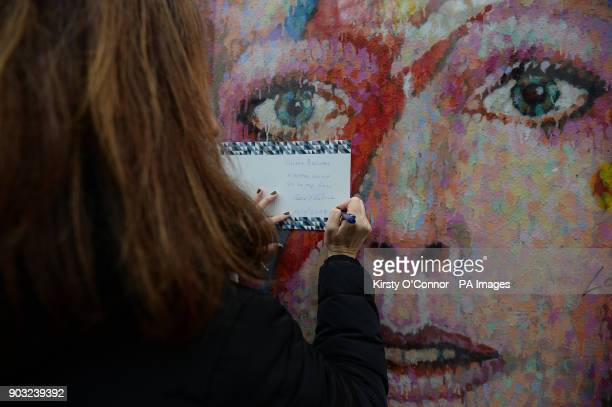 A woman writes a Happy Birthday card to David Bowie at a mural of the singer in Brixton London on the second anniversary of his death
