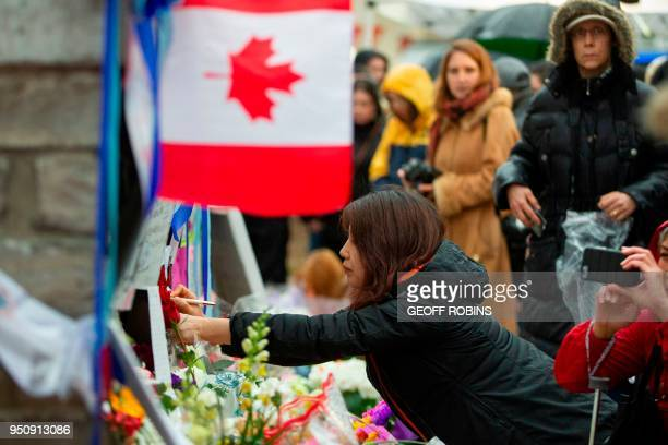 A woman writes a message at a memorial on April 24 2018 in Toronto Canada near the site of the previous day's deadly street van attack A van driver...