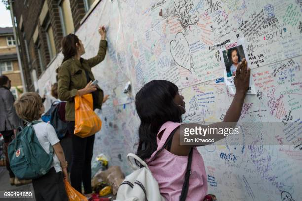 A woman writes a message on a wall of condolence outside Latymer Community Church on June 16 2017 in London England 17 people have been confirmed...