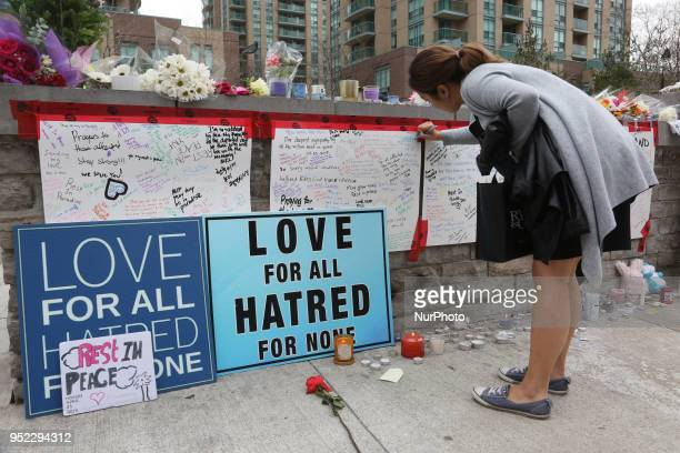 Woman writes a message on the memorial at Olive Square the day after 10 people were killed and 15 people injured in a deadly van attack in Toronto...