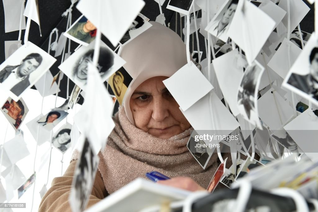 TOPSHOT - A woman writes a note in the golden book inside the memorial of victims, in front of the International Criminal Tribunal for the former Yugoslavia (ICTY) in The Hague, on November 22, 2017, prior to the verdict in the genocide trial of former Bosnian Serbian commander Ratko Mladic. Dubbed 'The Butcher of Bosnia,' Mladic's trial is the last before the ICTY, and the judgement has been long awaited by tens of thousands of victims across the bitterly-divided region, seeking to close a chapter in the brutal 1990s Balkans conflicts. /