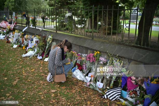 A woman writes a note in tribute to victims outside the Botanical Gardens in Christchurch on March 16 after a shooting incident at two mosques in...