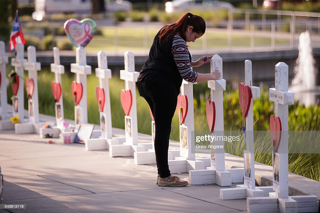 A woman writes a note on a cross at a memorial with wooden crosses for each of the 49 victims of the Pulse Nightclub, next to the Orlando Regional Medical Center, June 17, 2016 in Orlando, Florida. The shooting at Pulse Nightclub, which killed 49 people and injured 53, is the worst mass-shooting event in American history.