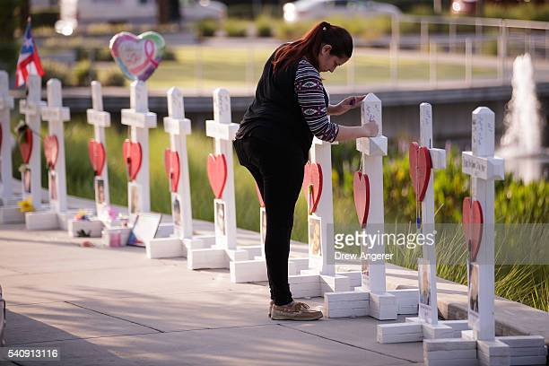 A woman writes a note on a cross at a memorial with wooden crosses for each of the 49 victims of the Pulse Nightclub next to the Orlando Regional...