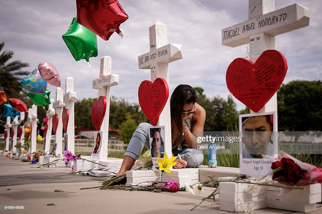 A woman writes a note on a cross for Eric Ivan Ortiz-Rivera at a memorial with wooden crosses for each of the 49 victims of the Pulse Nightclub, next to the Orlando Regional Medical Center, June 17, 2016 in Orlando, Florida. The shooting at Pulse Nightclub, which killed 49 people and injured 53, is the worst mass-shooting event in American history.